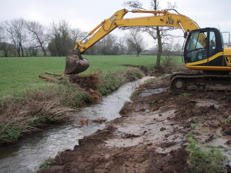Excavator installing root wads into the brook and re-profiling the banks